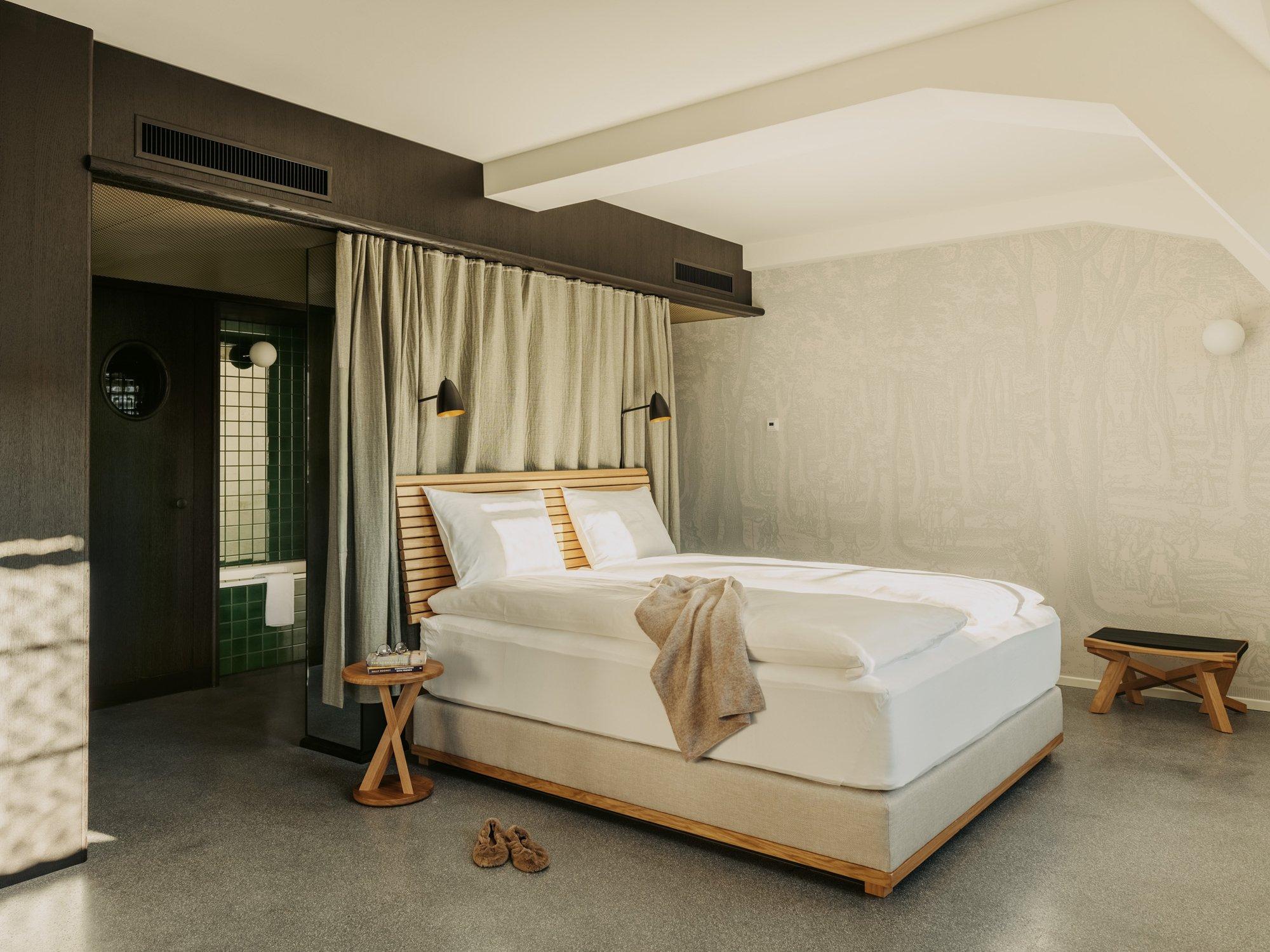 Die Betten sind mit den Kopfenden ebenfallszu freistehenden Trennwändenausgerichtet. Schwere Vorhängekönnen entlang von Deckenschienen zur Seite geschoben werden, um den Eingang zum Schlafbereich abzutrennen.