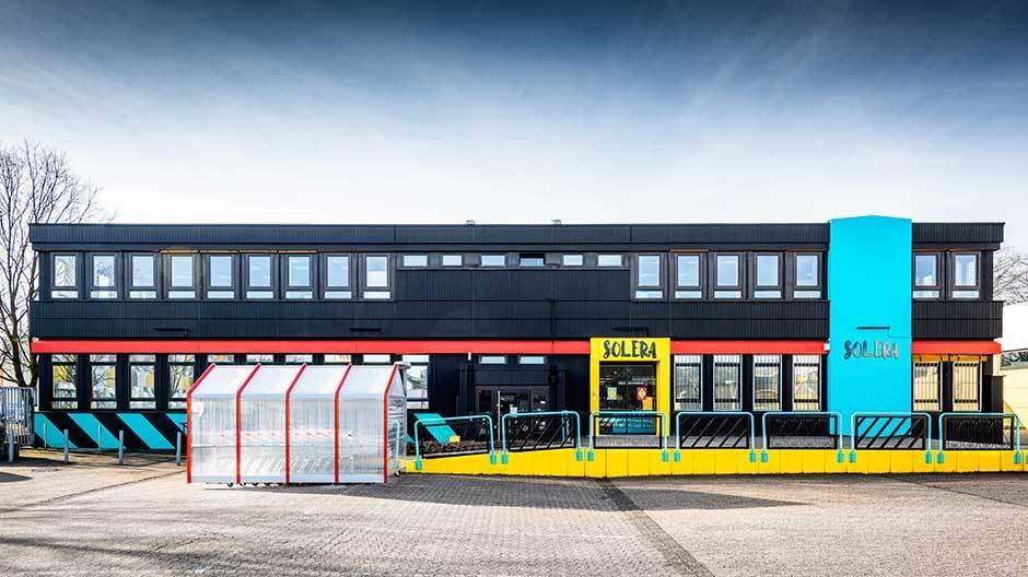 Die orthogonale Silhouette des Baus wird durch einen horizontalen roten Blockstreifen und ein senkrechtess Rechteck mit dem Solera-Logo unterstrichen, während der Eingang des ansonsten schwarzen Gebäuderiegels gelb umrahmt ist.