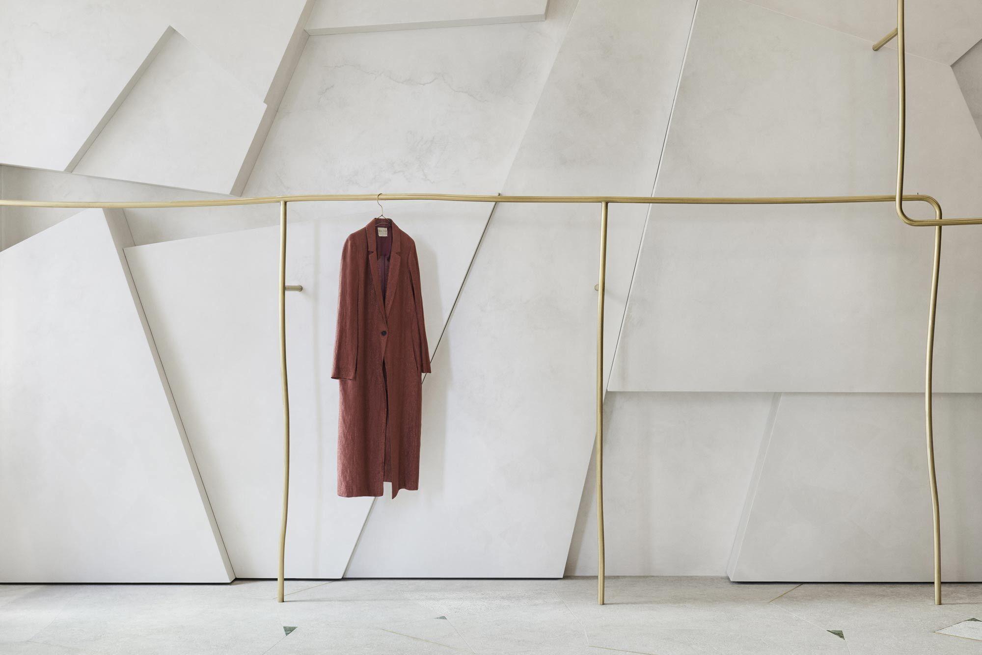 Kleiderstangen aus unregelmäßig geformtem Messing setzen die Mode von Forte Forte in Szene.