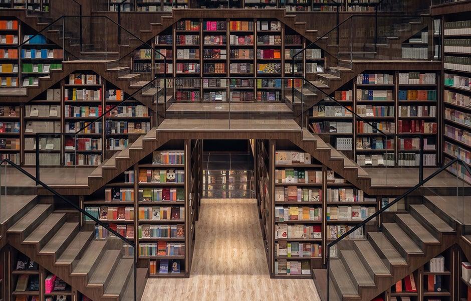 Der hohe Raum splittet sich auf viele Ebenen auf. Der Weg wird von Bücherregalen flankert, der Besucher kann überall stöbern und verweilen.
