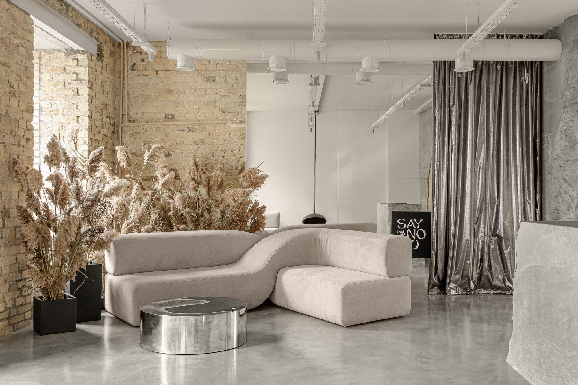 Auf schimmernde Nuancen setzt ein silbriger Vorhang, der vor einer verspiegelten Wand platziert ist und die Illusion eines dahinter liegenden Raumes erweckt.