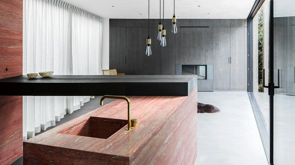 Mit einem Tresen aus Marmor und Messingarmaturen von Vola entwarf Innenarchitekt Arjaan De Feyter ein belgisches Ferienhaus für die Entspannung – und die Ewigkeit.