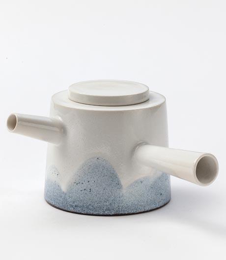 Der dänische Keramiker Lars Renk bringt blaue Wölkchen auf die Keramik-Oberfläche.