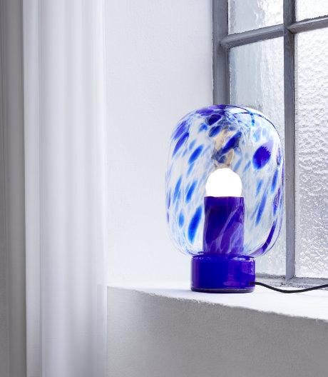 Die gläserne Tischleuchte spielt mit Transparenz, Licht und Farbe.